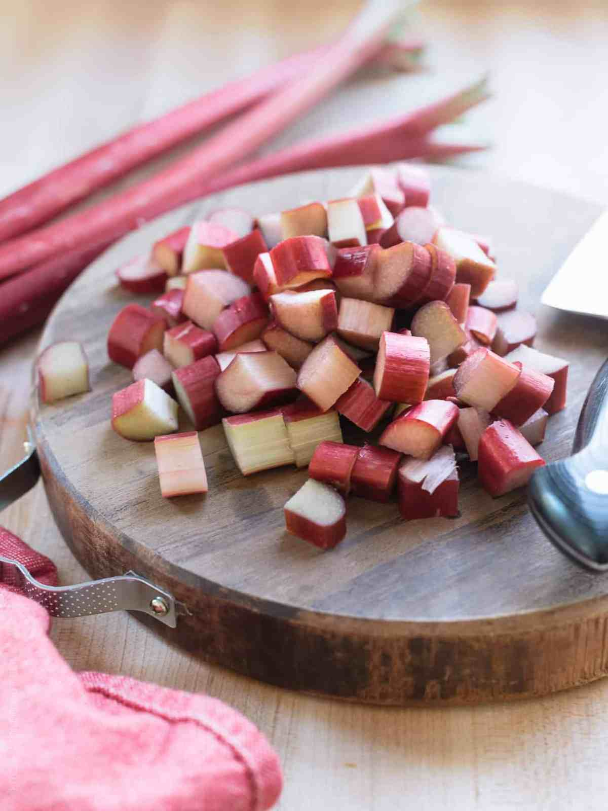 Chopped rhubarb on a wooden board with stalks of rhubarb in the background.