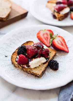 Toast topped with burrata cheese and balsamic berries on a white plate.