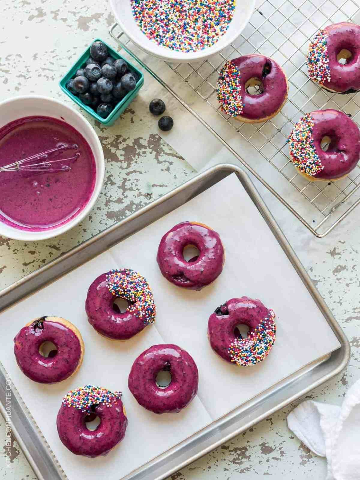 Baking tray of Blueberry Lemon Glazed Baked Donuts with sprinkles on top.