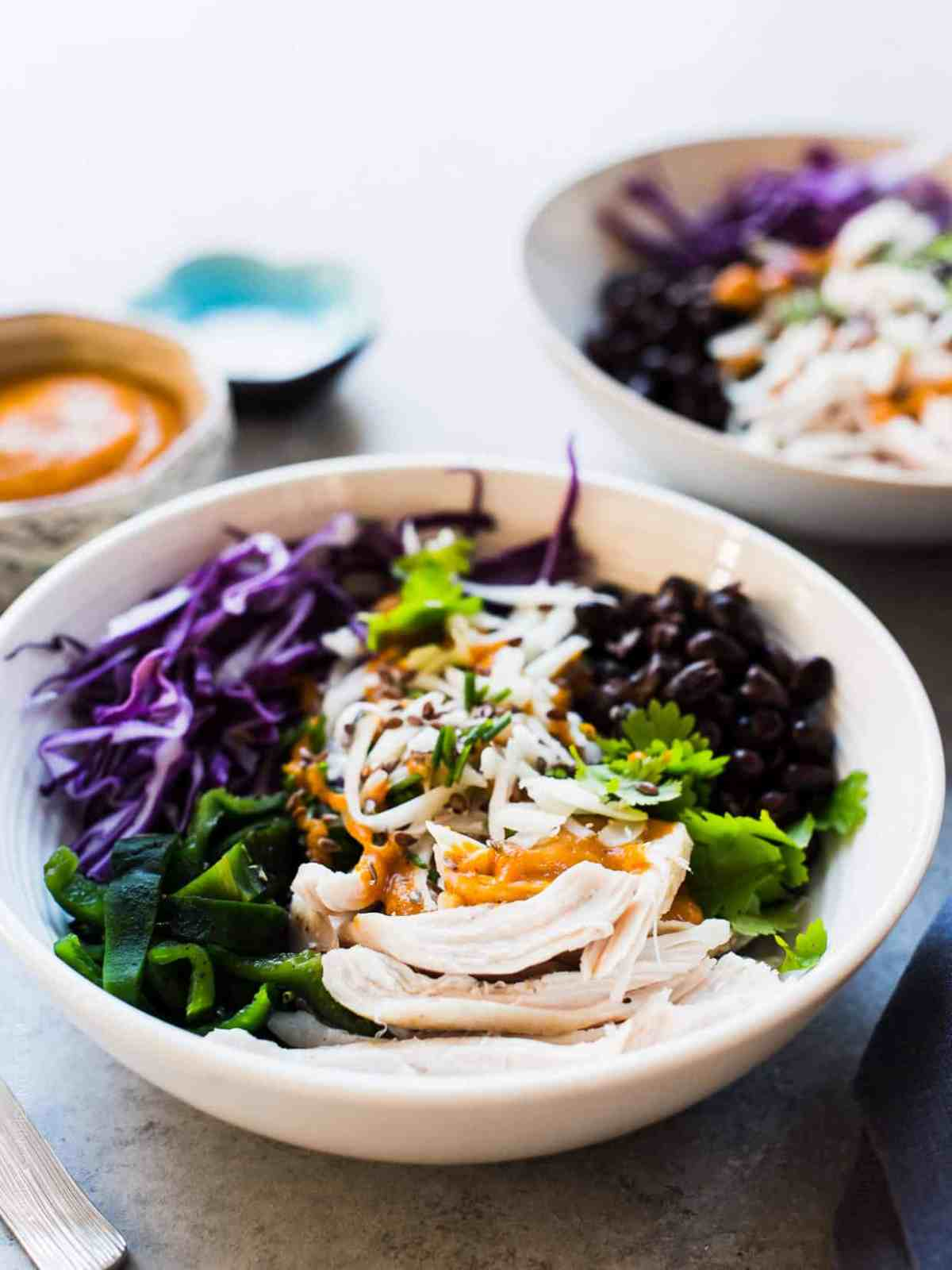 A fresh salad prepared with shredded chicken, cabbage, black beans, charred poblanos, and pumpkin-red curry vinaigrette served in a white bowl.