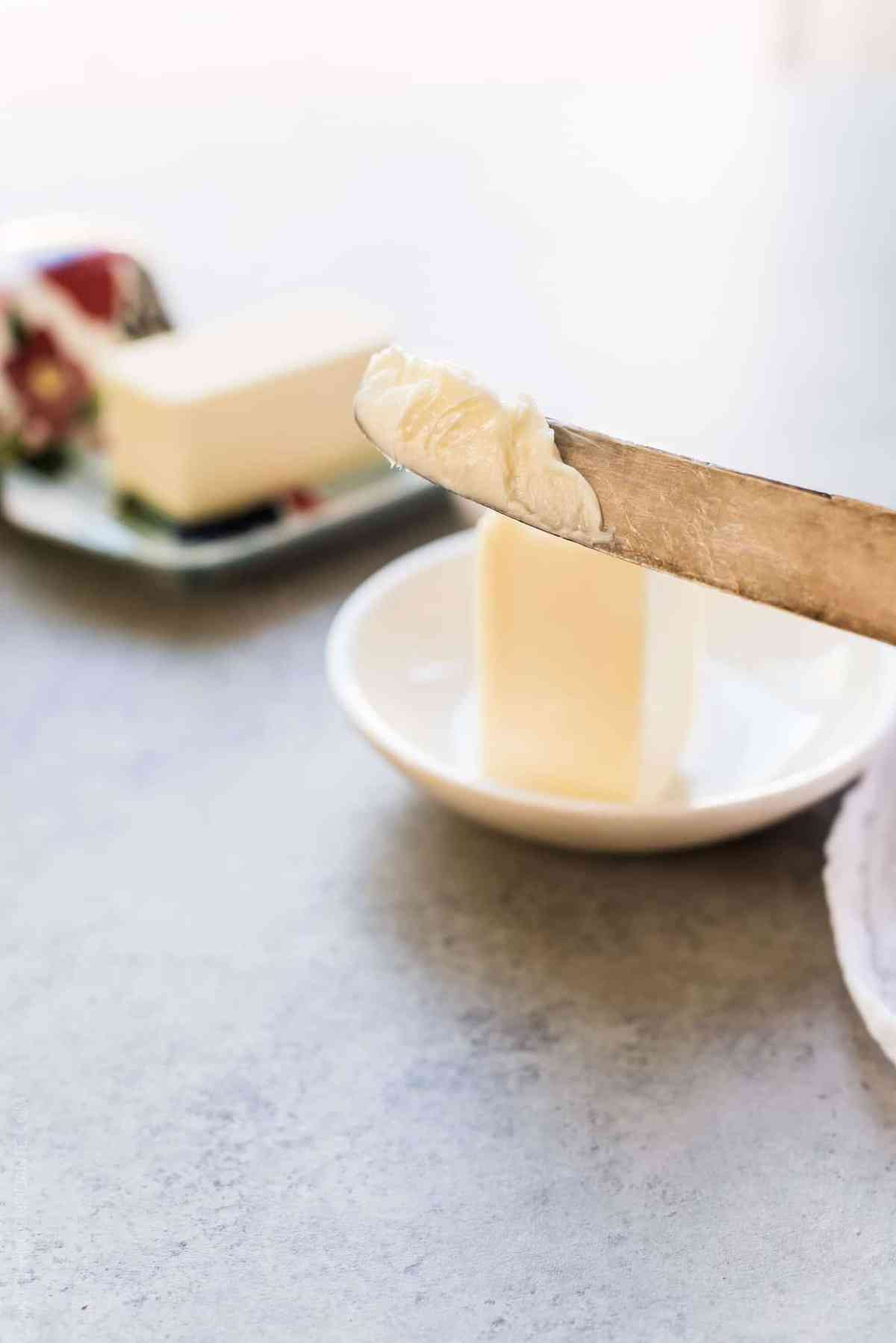 Butter knife with softened butter on it and a stick of butter in the background.