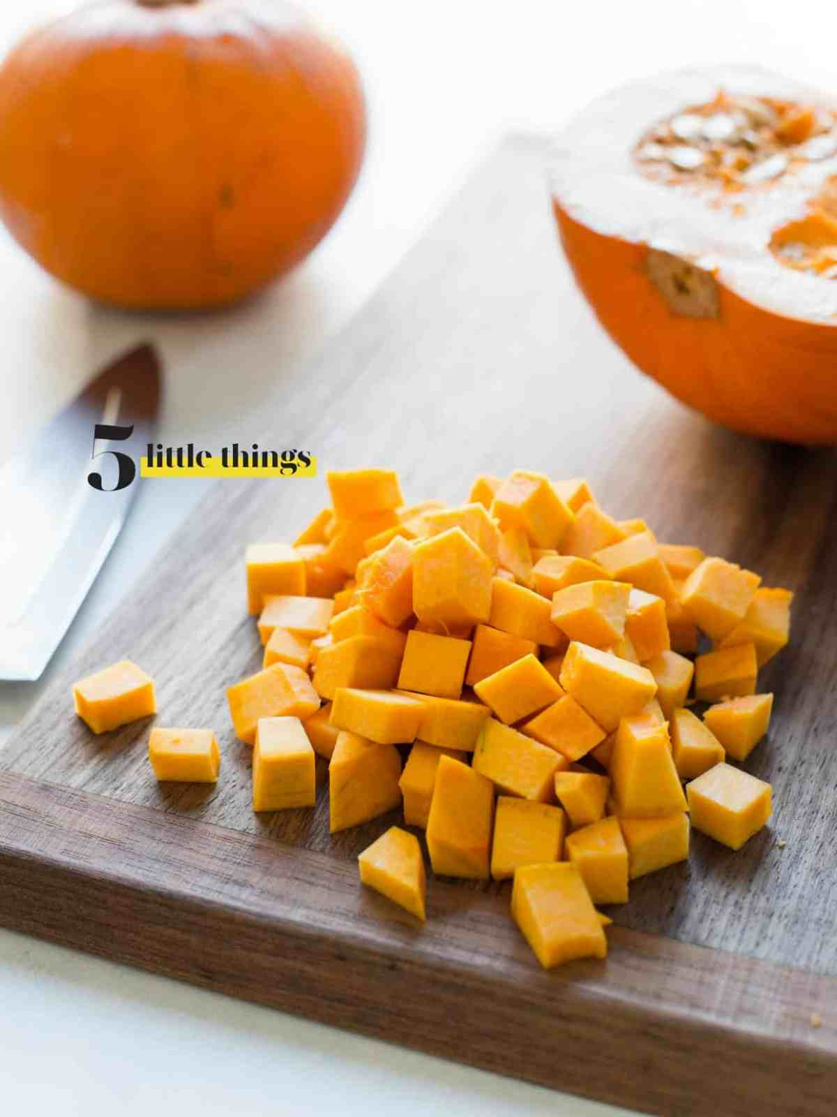 Diced Pumpkin on a wooden cutting board.