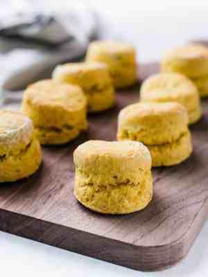 Freshly baked Pumpkin Cheddar Biscuits on a wooden serving board.