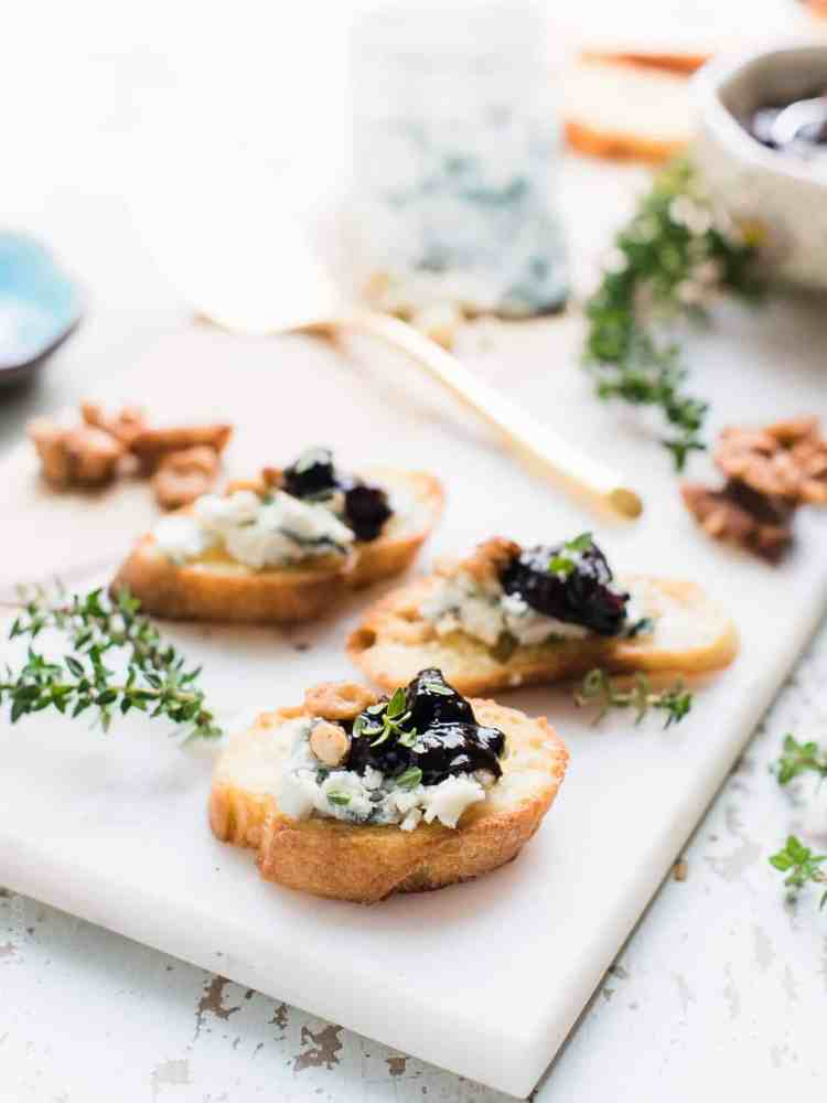 Crostini with Gorgonzola and Prune Chutney plated on a white serving board with sprigs of fresh thyme surrounding.