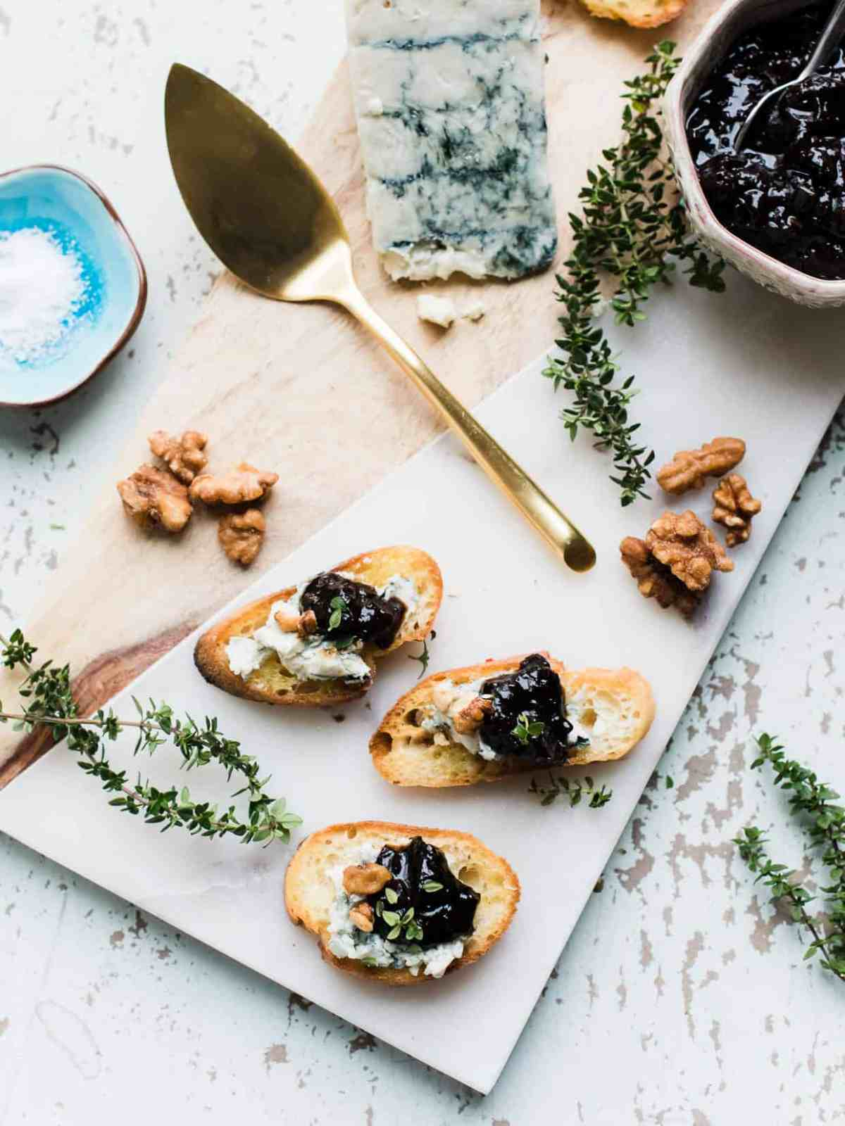 Overhead view of Crostini with Gorgonzola and Prune Chutney plated on a white serving board with sprigs of fresh thyme, walnuts and Gorgonzola cheese surrounding.