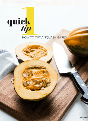 Acorn squash on a wooden cutting board cut in half with a chef's knife.