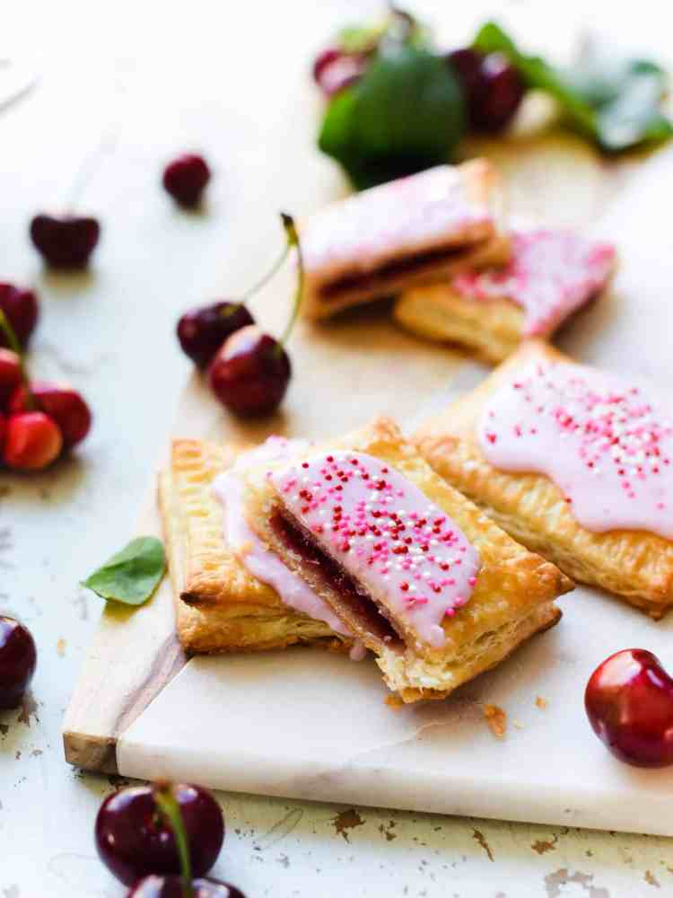 Inside view of Homemade Cherry Pop Tarts stacked on a marble and wood serving board with fresh cherries.