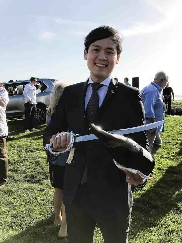 A man in a black suit holding a champagne bottle and saber at the Pebble Beach Food & Wine 2017.