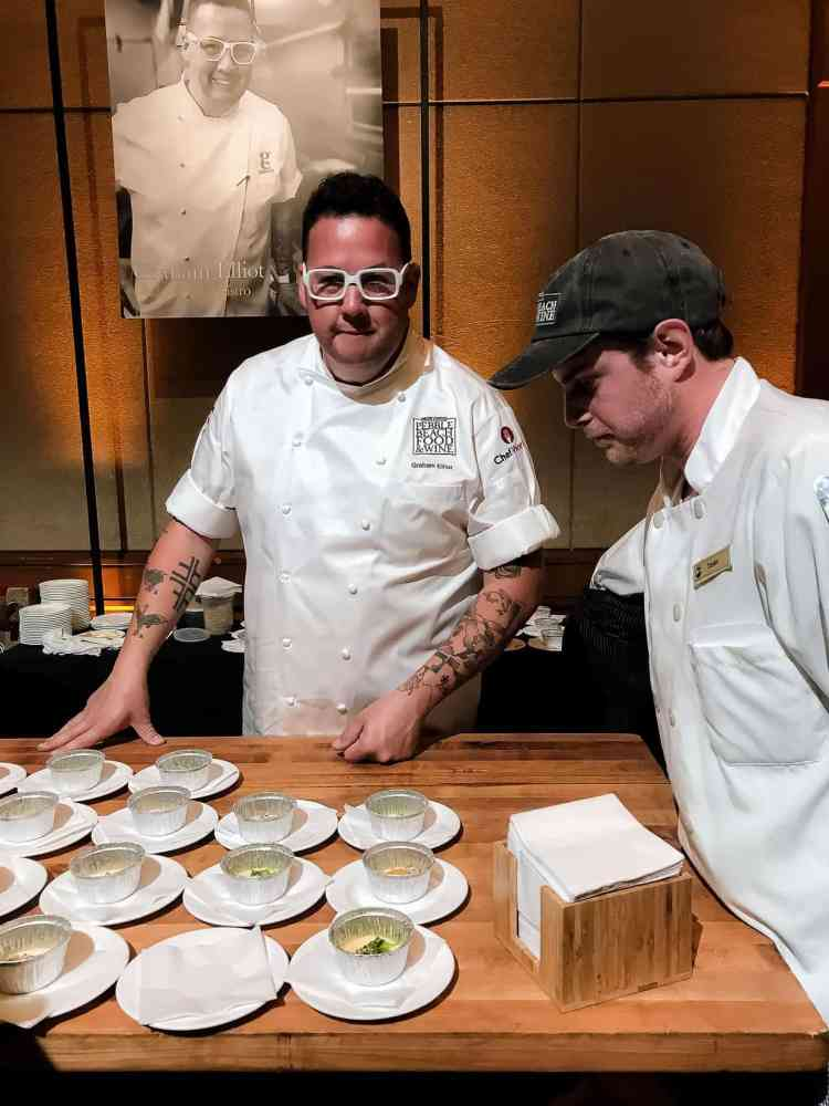 Two men in white chefs coats standing by small plates of food on a wooden table at the Pebble Beach Food & Wine.