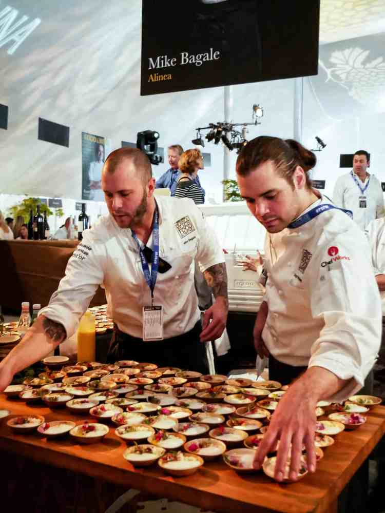 Two men arranging small bowls of appetizers at the Pebble Beach Food & Wine.