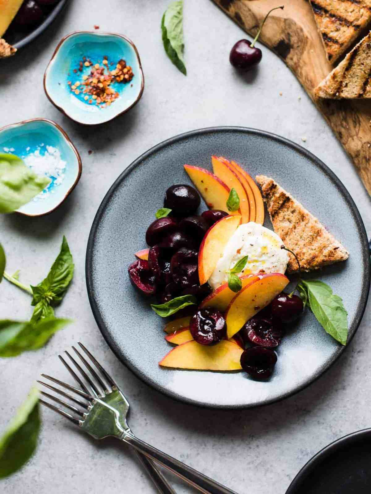 Peaches, cherries, burrata, and basil on a teal plate surrounded by fresh basil and grilled bread.
