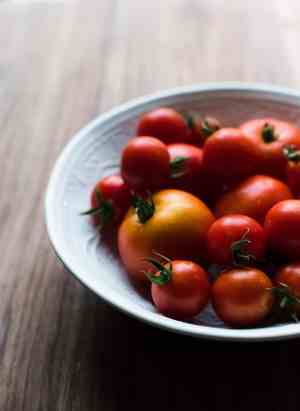A white bowl filled with red tomatoes.