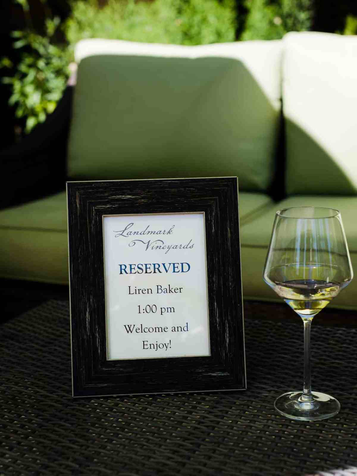 A small photo frame marking a reserved table at a wine tasting.