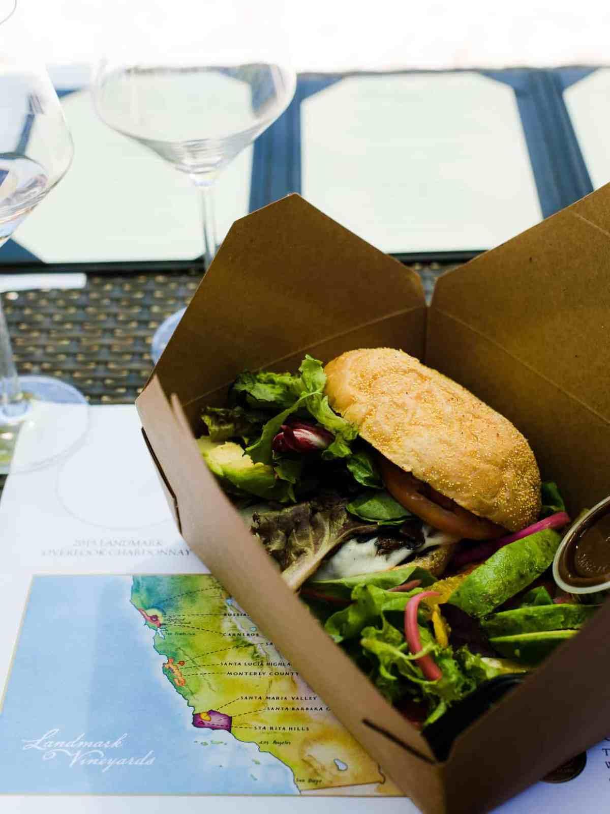A portobello mushroom burger in a cardboard takeout box.