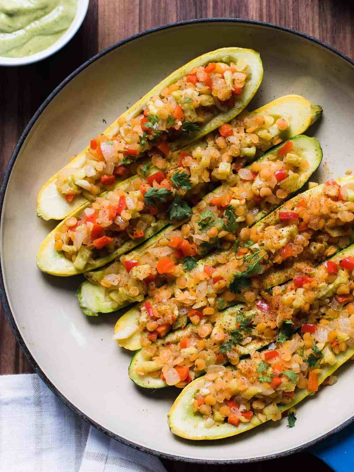 Stuffed yellow squash and zucchini with a tasty lentil filling in a shallow pan.