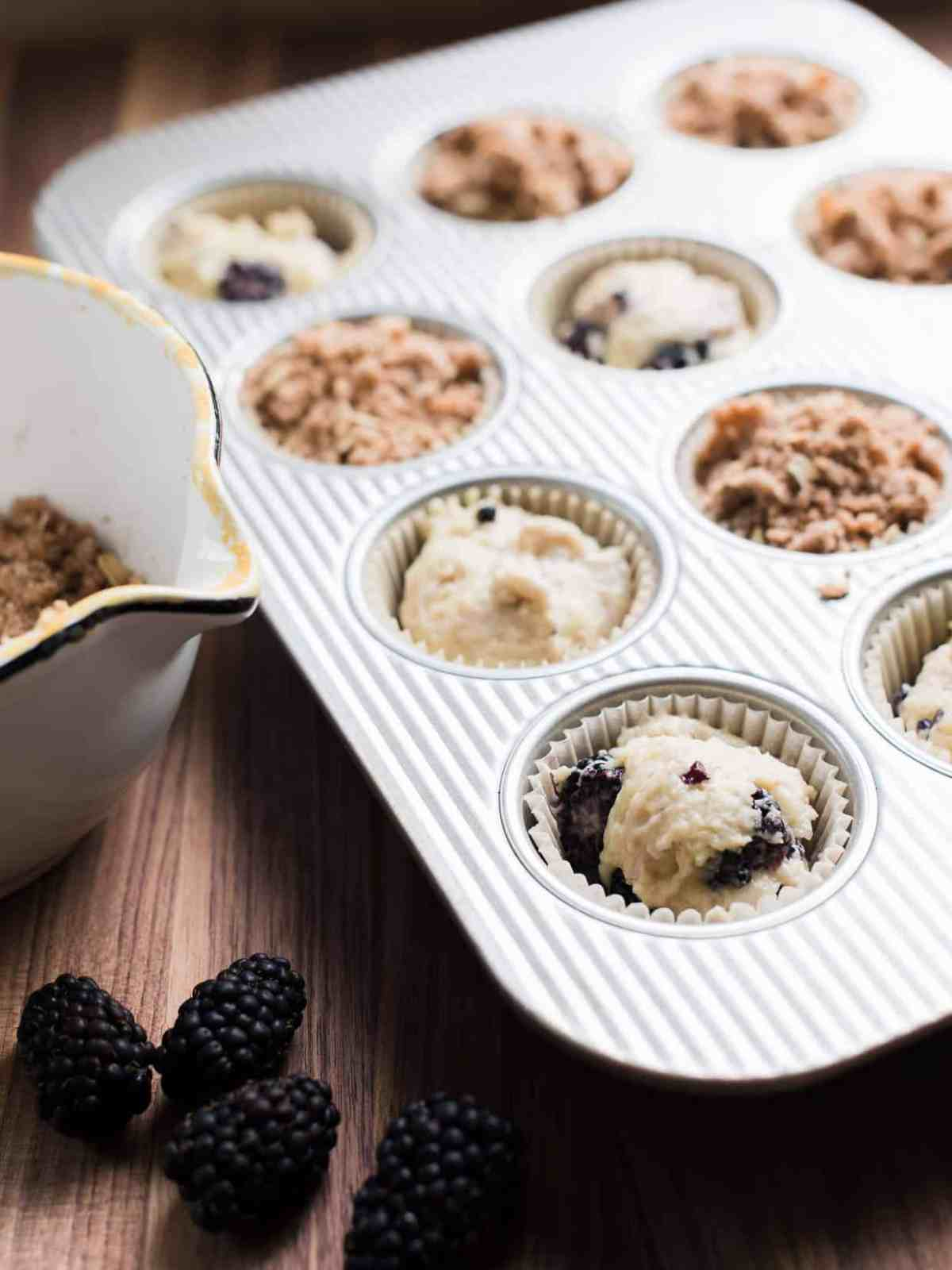 Muffin tin filled with Blackberry Yogurt Muffins ready to be baked.