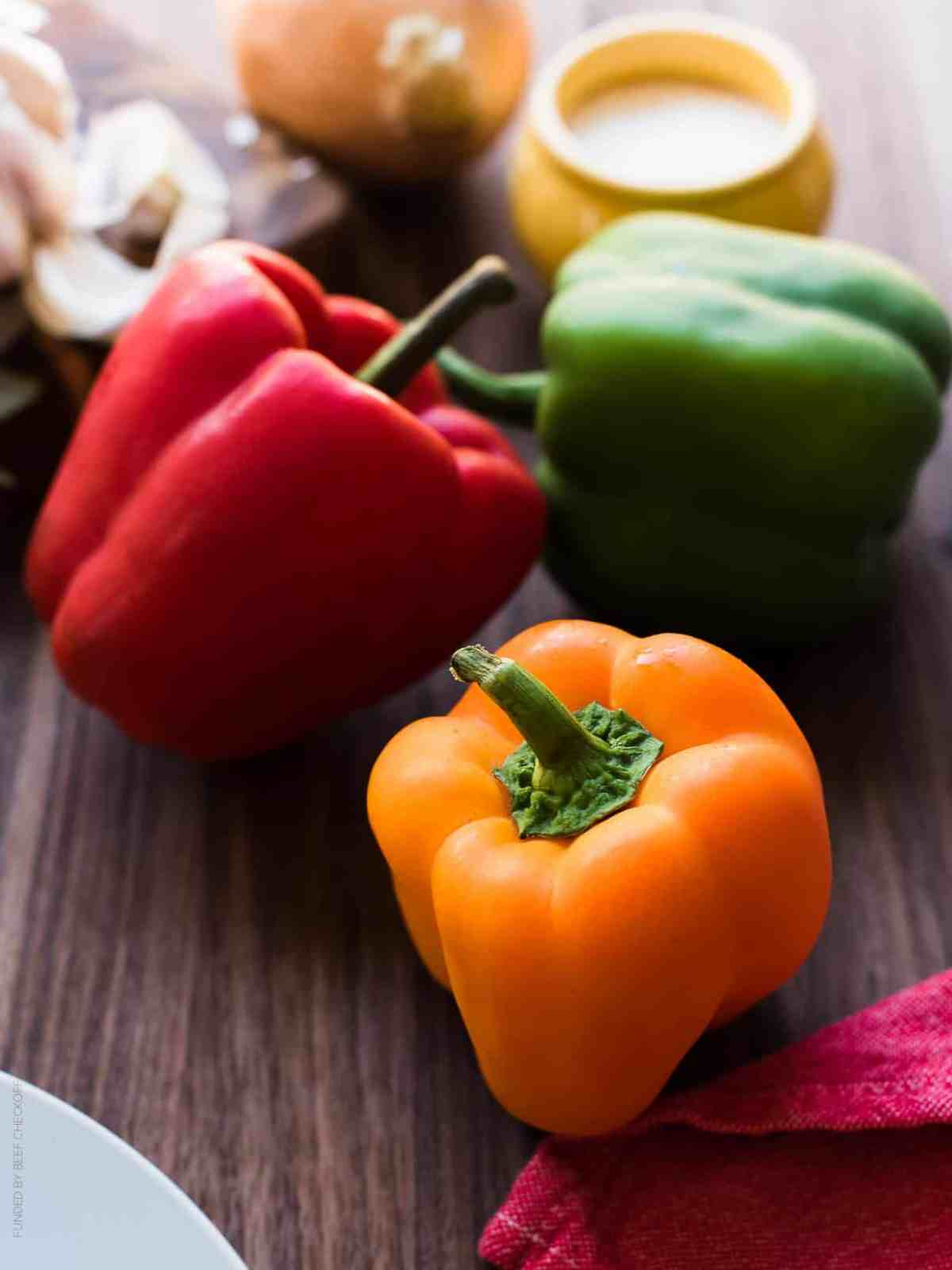 Orange, red, and green bell peppers on a wooden surface.