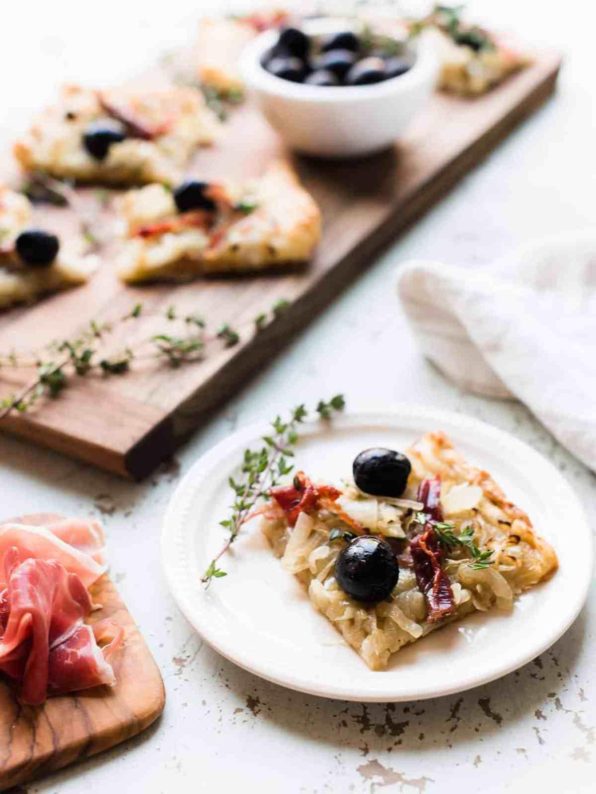 Slice of homemade Pissaladière with Prosciutto on white plate with more slices on a wooden serving board in the background.