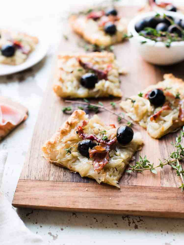 Slices of homemade Pissaladière with Prosciutto on a wooden serving board.