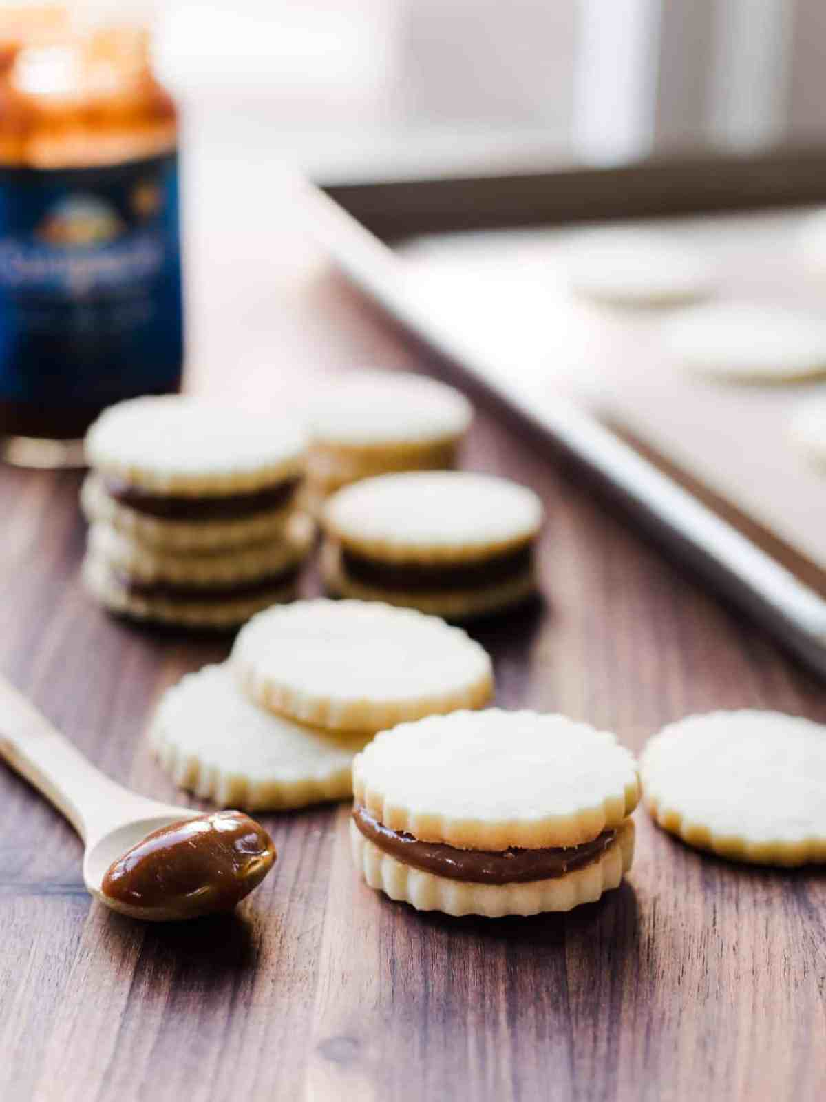 Spoon filled with dulce de leche surrounded by Alfajores cookies.
