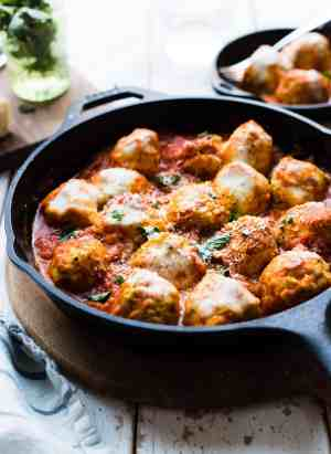Chicken Parmesan Meatballs with melted cheese in a cast iron skillet
