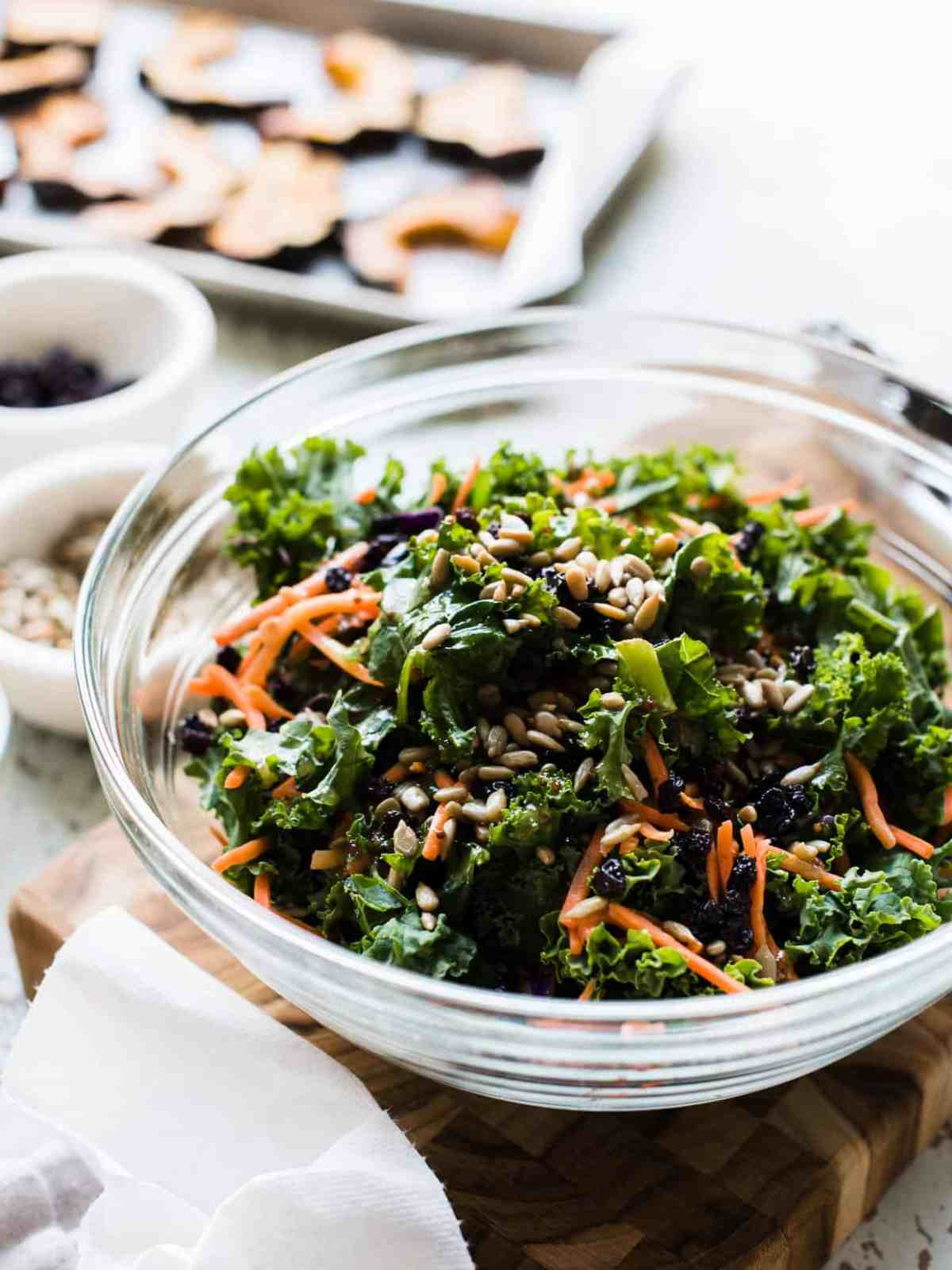 Kale salad with carrots, currants, and sunflower seeds in a glass bowl for Roasted Acorn Squash and Kale Salad.