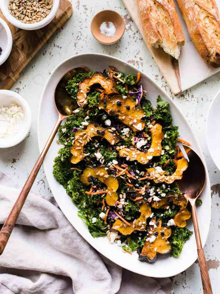 Roasted acorn squash over kale, with sunflower seeds, currants and a maple vinaigrette on a white serving platter.