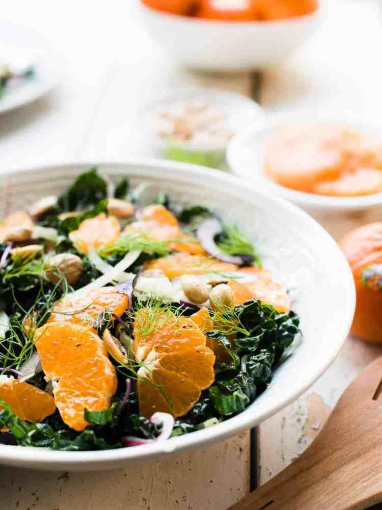 Slices of mandarin oranges on a bed of kale with fennel in Mandarin Orange Kale Salad.