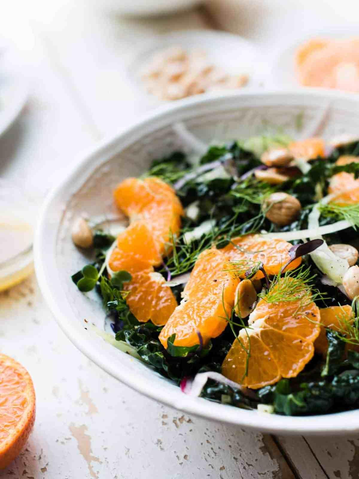Juicy mandarin orange slices top kale salad in white bowl