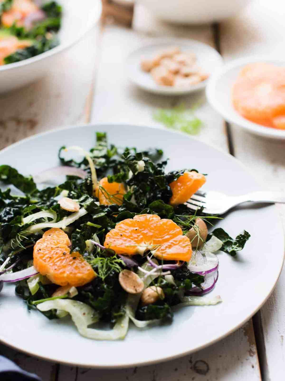 Serving of mandarin orange kale salad on a light blue salad plate