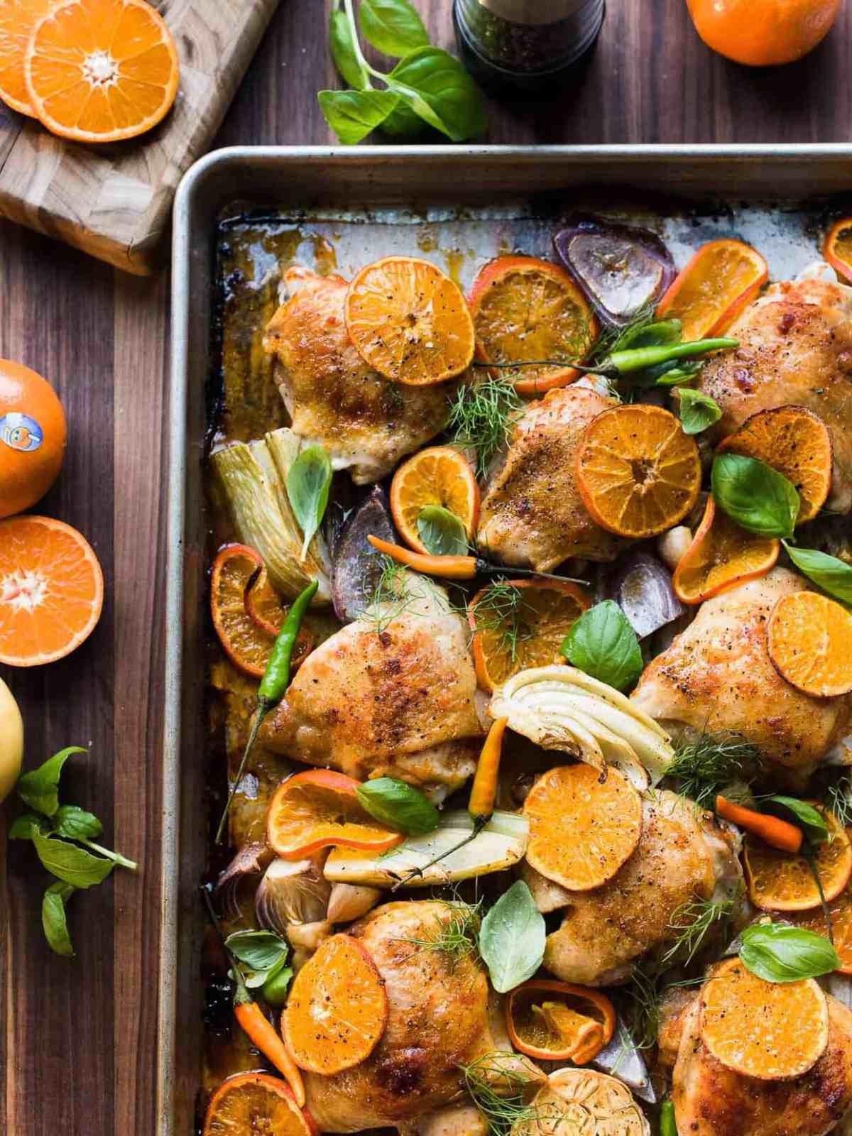 Baking sheet with Thai-spiced Mandarin Orange Roasted Chicken Thights, fennel, onion, and garlic.