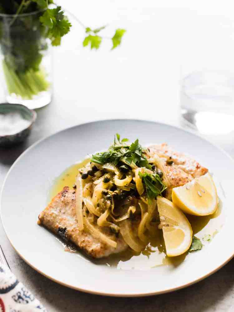 Grilled mahi mahi fish topped with onions, caper, cilantro and slices of lemon.
