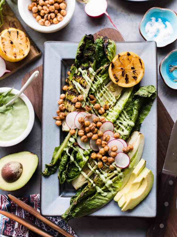 Grilled Romaine Green Goddess Salad on grey platter with avocado, radish, chickpeas and grilled lemon.