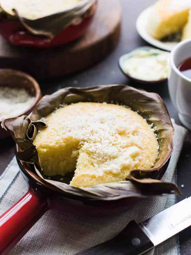 Bibingka - Filipino Coconut Rice Cake baked in banana leaves in a red terra cotta dish.