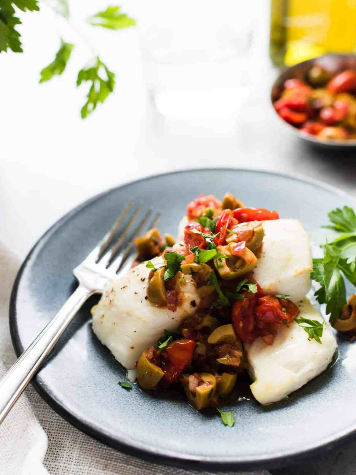 Grey plate with baked halibut topped with olives and tomatoes.