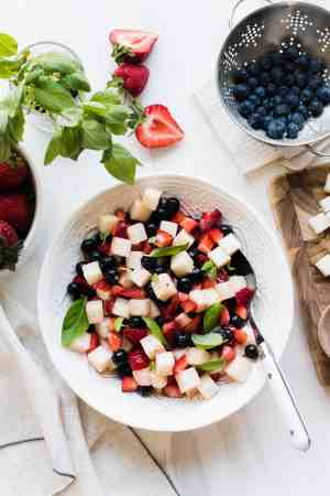 Strawberries, blueberries, and crispy jicama come together for a super simple, patriotic, and barbecue-ready Red, White and Blue Berry Jicama Salad in a white bowl.