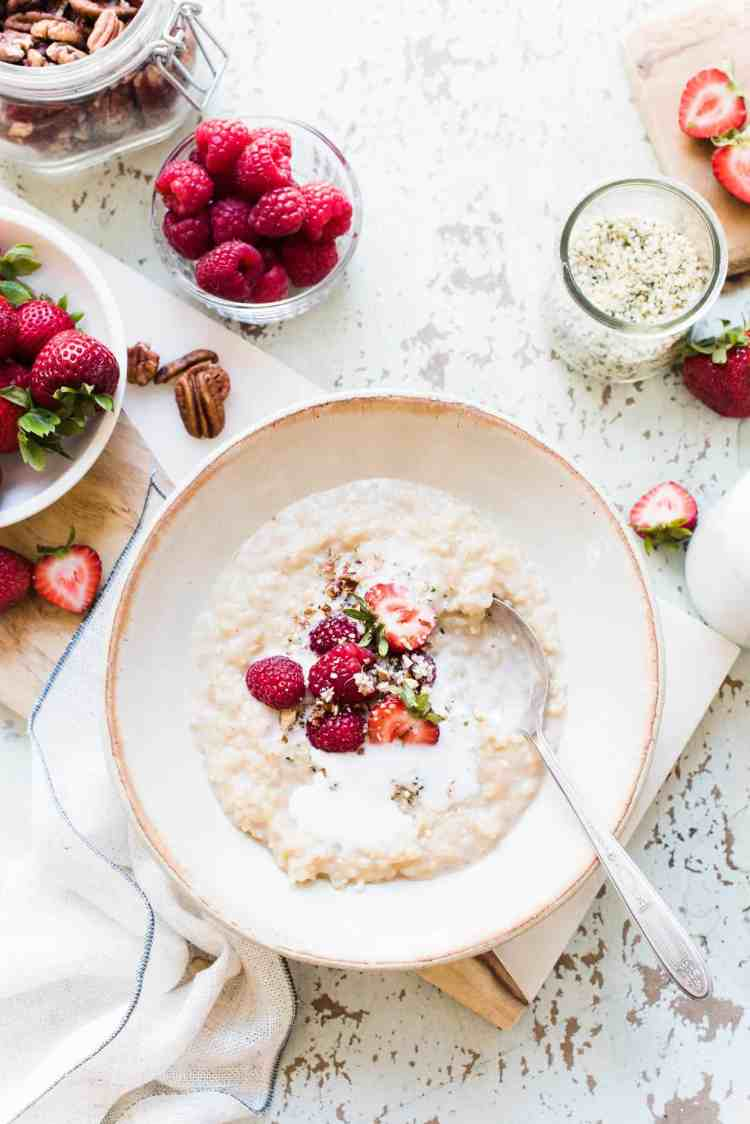 Bowl of Chai Coconut Brown Rice Pudding with strawberries, raspberries, flaxseed, pecan nuts for breakfast.