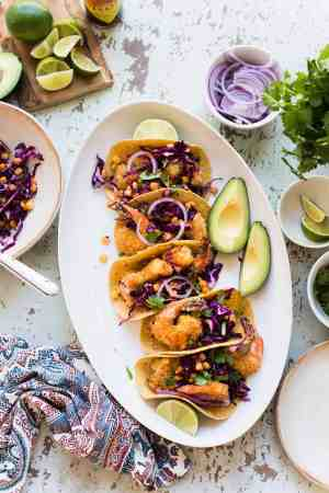 A platter with Oven-Fried Crispy Shrimp Tacos with Pickled Cabbage and Corn.