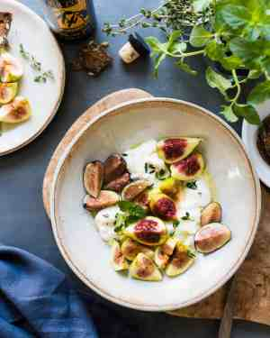 Cream bowl with torn burrata, sliced figs, herbs and a honey-balsamic glaze in a recipe for Honey Balsamic Figs with Burrata Cheese.