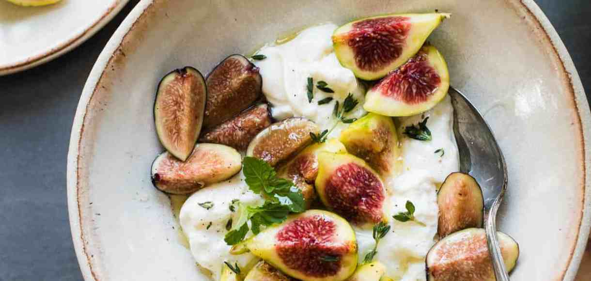 Slices of honey-balsamic figs with burrata with fresh mint and thyme in a bowl.
