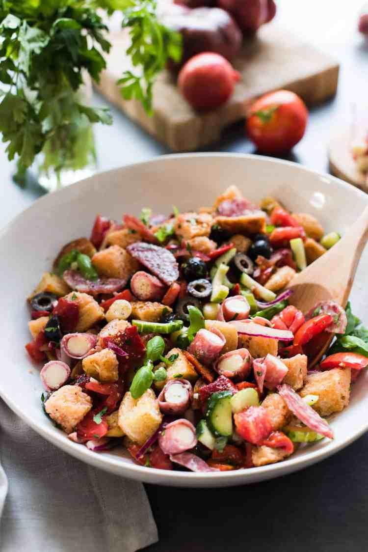 Muffuletta Panzanella Salad in a white bowl with bread, tomatoes, olives, salami, soppressata, and mozzarella cheese