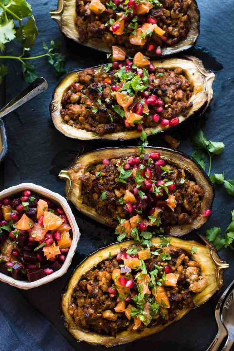 Stuffed Eggplant with Meat and Tahini is topped with a bright Orange Pomegranate Salsa on black slate board.