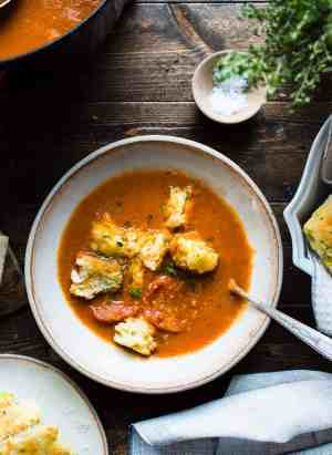 Bowl of Roasted Tomato, Garlic and Herb Soup with zucchini scones floating in soup on a wooden table.