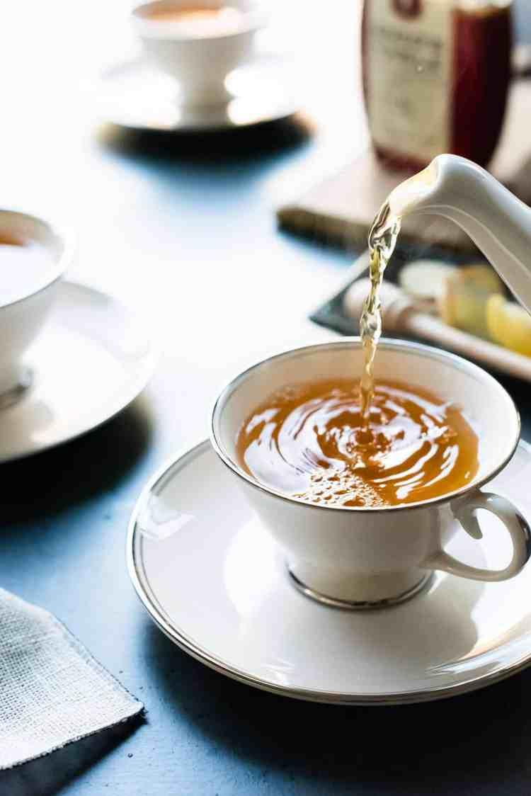 Tea kettle pouring homemade fresh ginger tea into a tea cup.