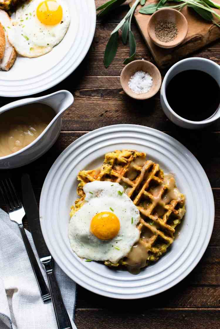 Mashed Potato and Stuffing Waffles with a sunny side up egg, served with gravy on a wooden table.