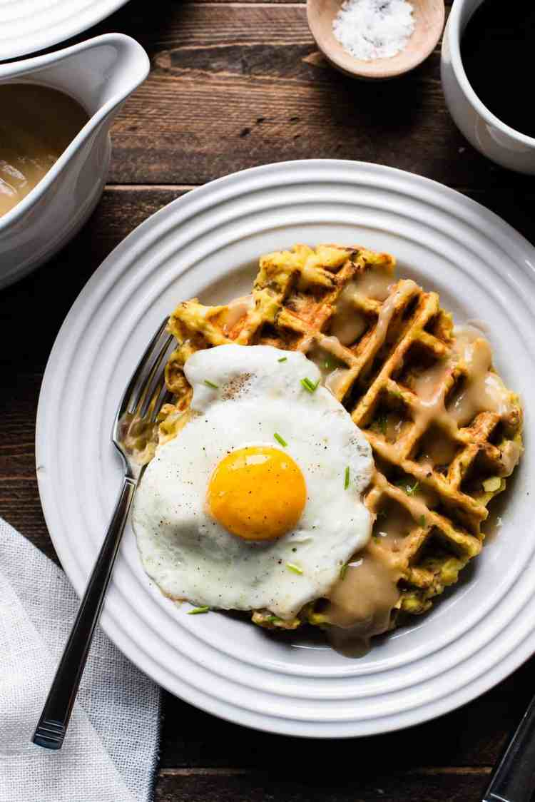 Mashed potato and stuffing waffles served with an egg and gravy.