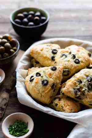 A parchment paper lined plate filled with Savory Olive Cheese Scones on a wooden table. Green and black olives in bowls in the background.