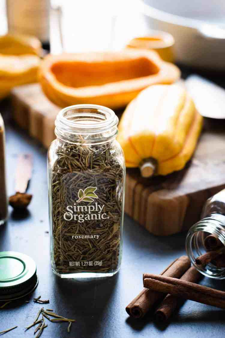Bottle of Simply Organic rosemary with delicata squash in the background.