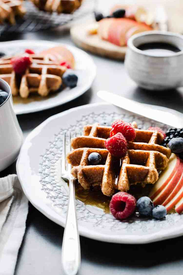 Apple Oatmeal Blender Waffles with syrup and fresh fruit.