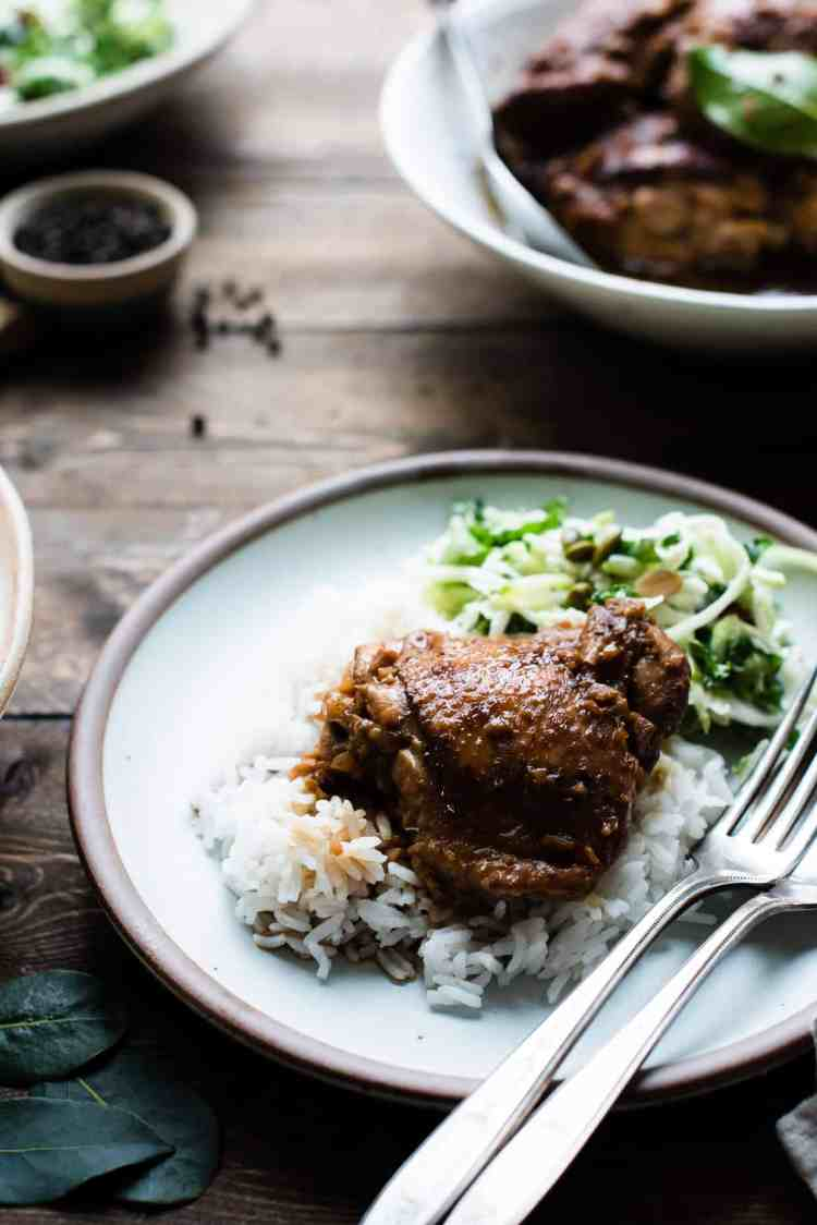 Instant Pot Chicken Adobo on a bed of rice on a plate.